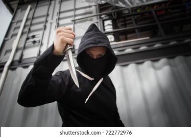 Masked criminal holding a knife