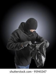 Masked criminal holding a stolen handbag