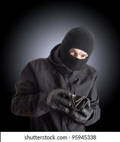 Masked criminal holding a stolen leather purse