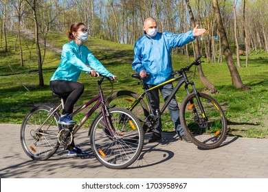 A masked cyclist shows the way to the masked girl.