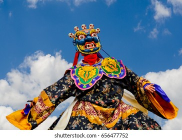 Masked Dancer -  Bhutan, masked dancer at a traditional monastery festival the Wangdue Phodrang Tsechu A monk in a colorful dress with mask during the tsechu (dance festival) in Wangdue, Bhutan.