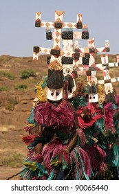 Masked Dogon dancers in a row, performing a ritual dance, wearing so-called kanaga-masks