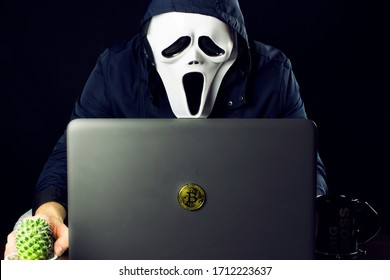 A masked hacker is sitting at a computer.