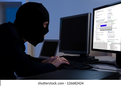 Masked hacker wearing a balaclava sitting at a desk downloading private information off a computer