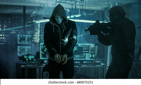 Masked Hacker Wearing Handcuffs is Guarded by Fully Armed Special Forces Soldier.  They're in Hacker's Hideout Basement with Multiple Operating Displays.