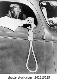 Masked Ku Klux Klan member, holds a noose outside a car window during a parade through an African American neighborhood of Miami on the night before a primary election in May 1939. - Shutterstock ID 242815225