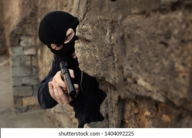 Masked man with gun hiding behind stone wall outdoors. Criminal offence