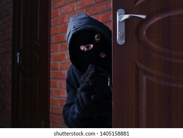 Masked man with gun spying behind open door indoors. Criminal offence