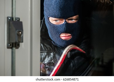 Masked Man Holding Crowbar While Looking Into House Window