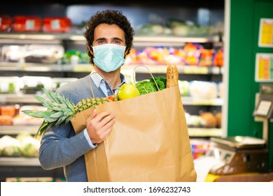 Masked man holding an healthy food bag in a supermarket during the coronavirus pandemic