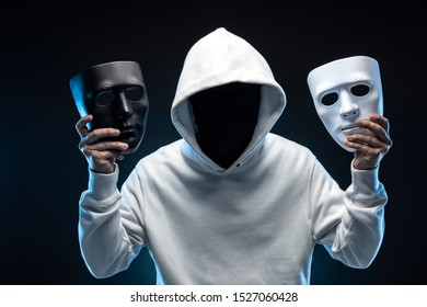 Masked man in hoodie. Dark background.