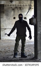 Masked man with knife, in ruined building