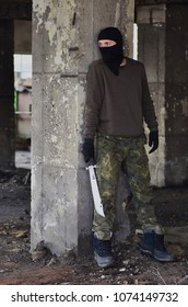 Masked man with machete, in ruined building, hiding behind the wall