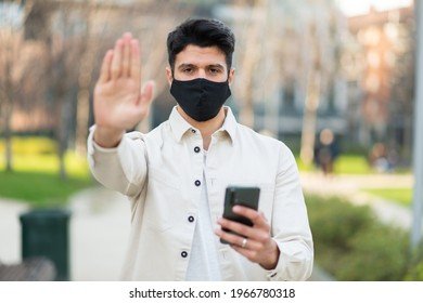 Masked man showing the stop sign, coronavirus pandemic social isolation, business halt and stay at home concepts - Shutterstock ID 1966780318