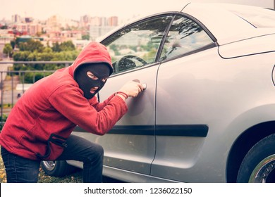 Masked man squats and breaks someone's car looking to the viewer. Thief in hoodie and hidden face makes attempt to picklock the parked vehicle fixing his eyes at camera. Evil-doer damages car lock.