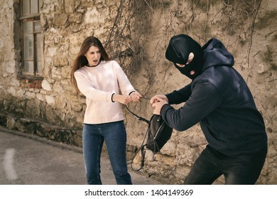 Masked man trying to steal woman's backpack outdoors. Criminal offence