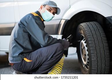 Masked mechanic checking the pressure of a van tire during coronavirus pandemic