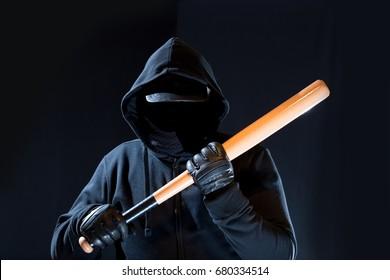 A masked person holding a baseball bat at night