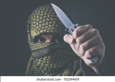 Masked terrorist treating with a knife. Concept of terrorism and violence.