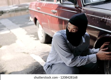 Masked thief in black balaclava trying to break into car. Criminal crime concept.