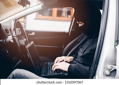 Masked thief hacker in a balaclava disarming car security systems and stealing a car