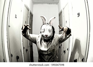 Masked woman in home interior scared rabbit