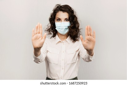 Masked woman makes stopping hand gesture. Influencer Girl blogger in medical mask talks about covid-19, coronavirus. Girl in medical mask stops 2019-nCov