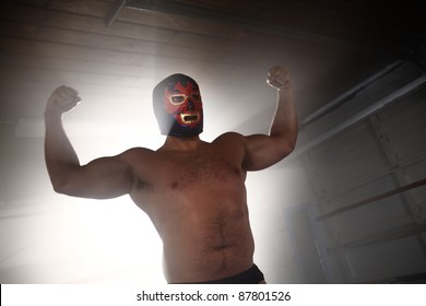 Masked wrestler flexing muscles