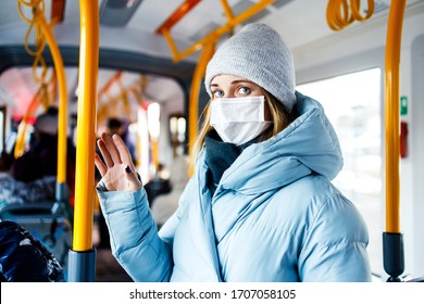 Maskierte junge Frau, die nachmittags in der Buslounge neben gelben Handläufen steht. Coronavirus-Pandemie