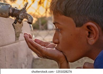 Maski, Karnataka, India - 26, March 2019 : Closeup of Child drinking water directly from corporation tap water in India.