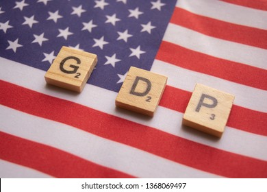 Maski,India 13,April 2019 :  Finance Concept, GDP or Gross domestic product wooden block letters on US Dollar flag