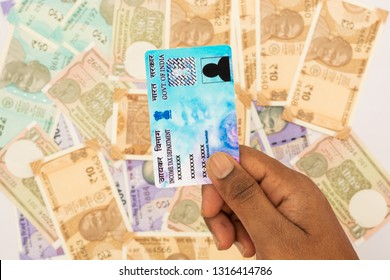 Maski,Karnataka,India - FEB,12,2019 : : Person holding PAN card on stack of Indian new currency notes