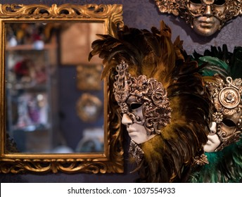 Masks handing on wall next to a mirror in a mask shop, Venice, during the Venice Carnival (Carnivale di Venezia) 2018.