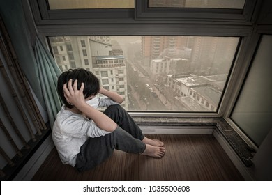 Mask-wearing boy looking outside the window on extremely polluted day in China