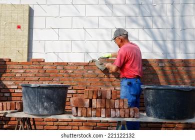Mason is bricklaying