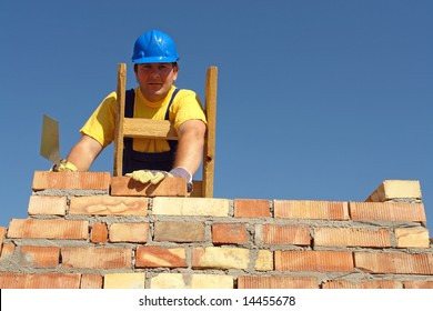 Mason building brick wall standing on wooden ladder
