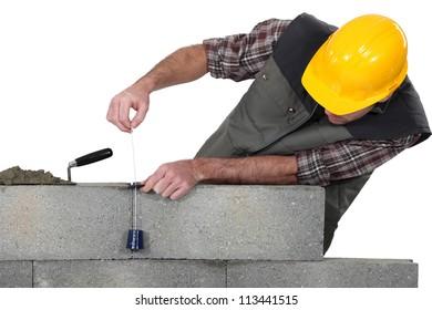 Mason building a bricks wall