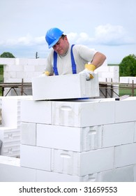 Mason building house walls from white aerated autoclaved concrete blocks