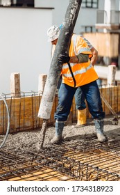 Mason building and worker using a automatic cement pump and leveling a first layer of fresh concrete floor at house, construction site