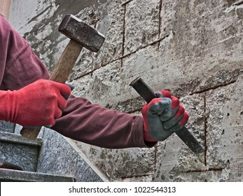 mason with chisel and hammer restores the concrete where the metal is rusty