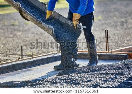 A mason directing the shute of a cement truck to pour the cement to make a cement slab