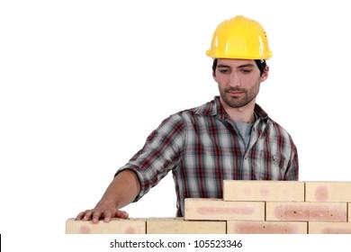 mason erecting a brick wall