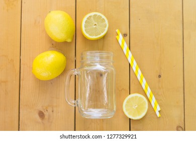 Mason glass jar , fresh lemons and straws on wooden table. Flat lay. Ready for cocktail.