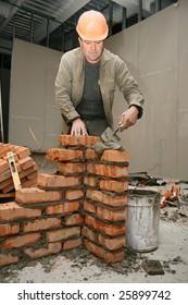 Mason in a hardhat building brick wall