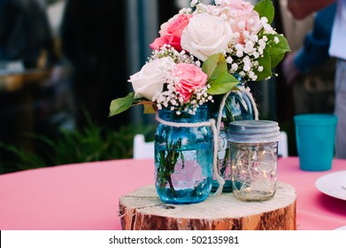 Mason jar bouquet centerpiece with roses at a lovely rustic wedding