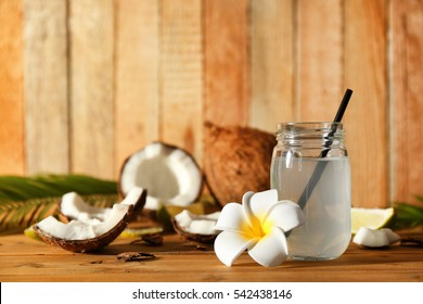 Mason jar with coconut water and beautiful plumeria flower on wooden background