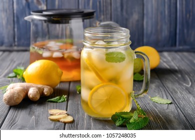 Mason jar of cold lemon tea with ginger on wooden table