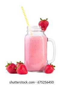 A mason jar with a comfortable handle and a beautiful pink milkshake in it. A glass of bright red strawberries around and on top of it and a yellow-white striped straw, isolated on a white background.