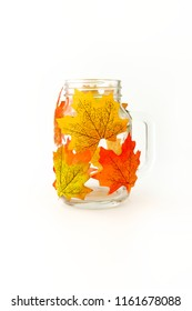 Mason jar decorated with artificial autumn leaves as tealight or candle holder and DIY autumn home decoration.