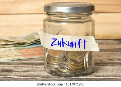 A mason jar, euro bills and coins and german word for future